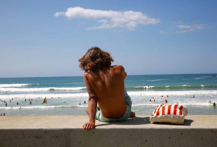 Shirtless man sitting at beach against sky