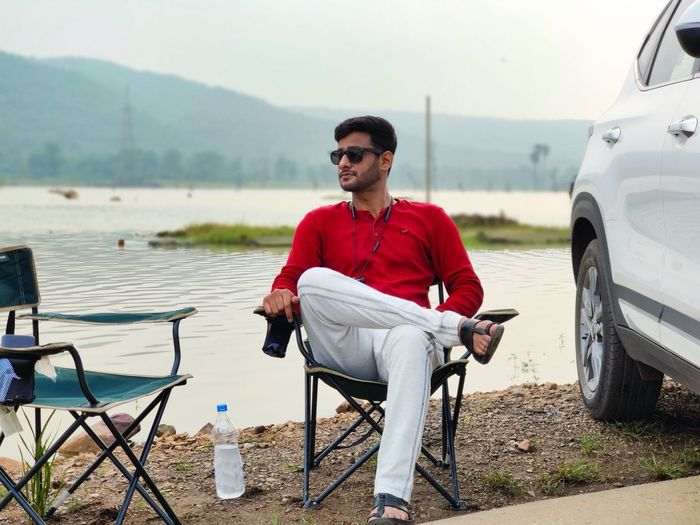 Young man sitting on chair at lakeshore