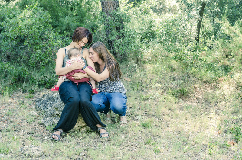 Full length of happy mother and daughter sitting on grass