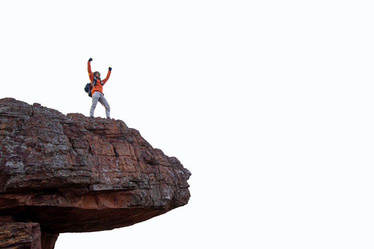 Man standing on rock against clear sky