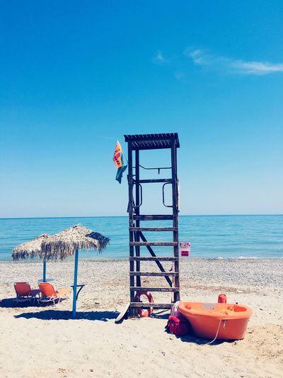 Lifeguard chair at beach against blue sky
