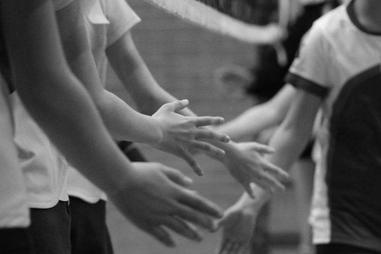 Midsection of boys giving handshake outdoors