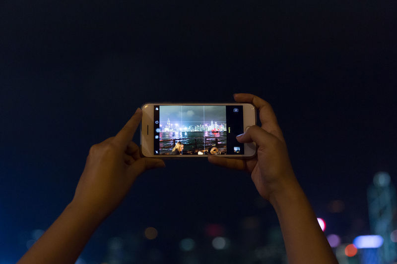 Midsection of woman photographing illuminated smart phone at night