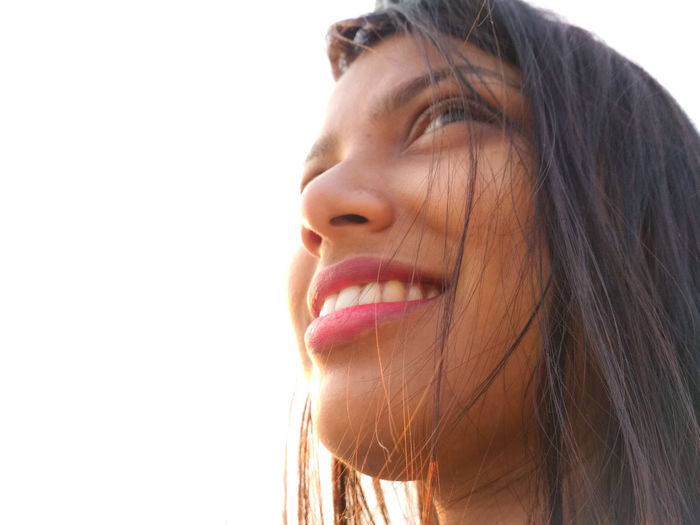 Close-up low angle view of smiling woman looking away against sky