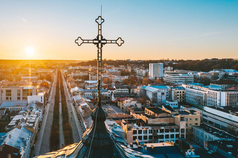Cross on tower against cityscape at sunset