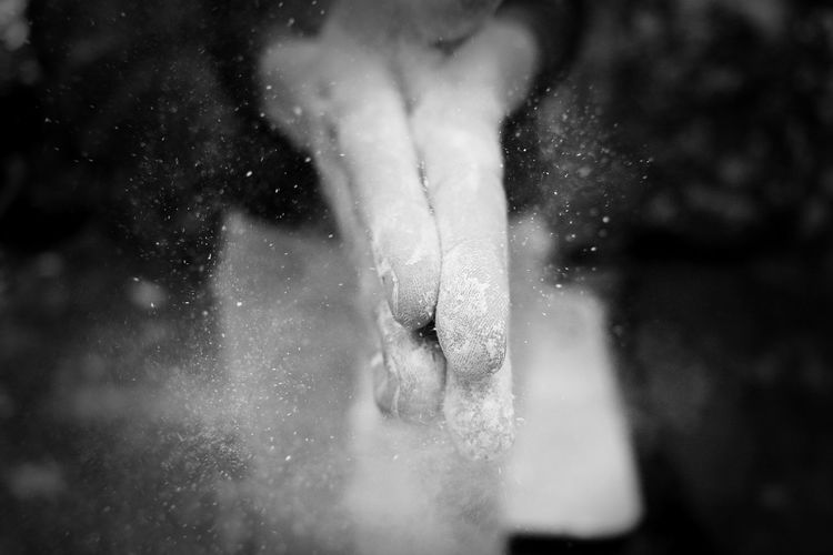 Cropped hands of person clapping while spreading powder
