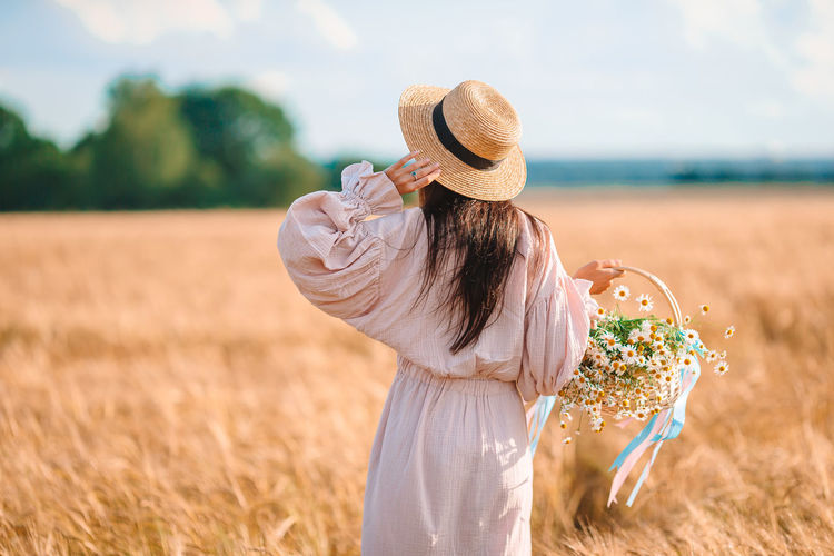 Rear view of woman holding flower standing on field