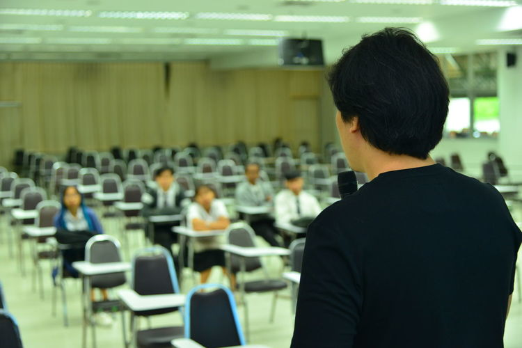 the man speaker Men Indoors  Group Of People Education Learning Meeting Corporate Business University Student Focus On Foreground Rear View In A Row Lecture Hall Seat Real People Presentation Speaker Business Auditorium