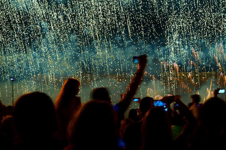 Crowd watching firework display at night