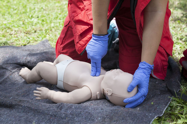 Midsection of person touching baby mannequin lying on grass field