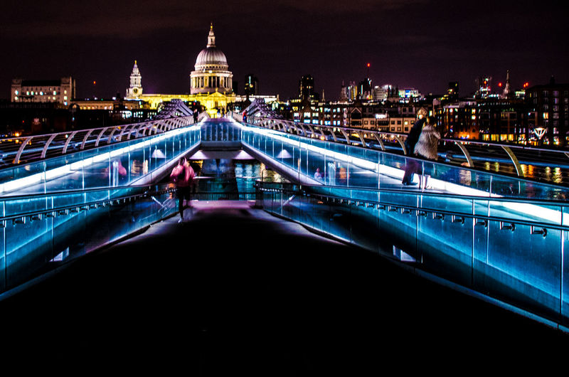 Light trails on bridge against buildings at night