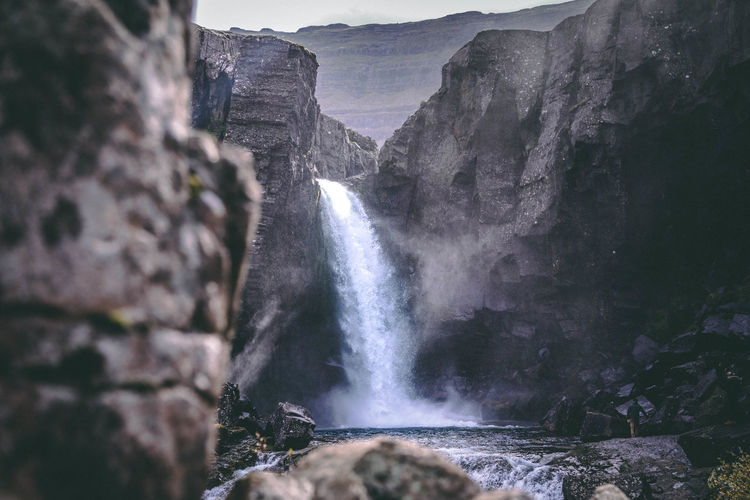 Scenic view of waterfall amidst mountains
