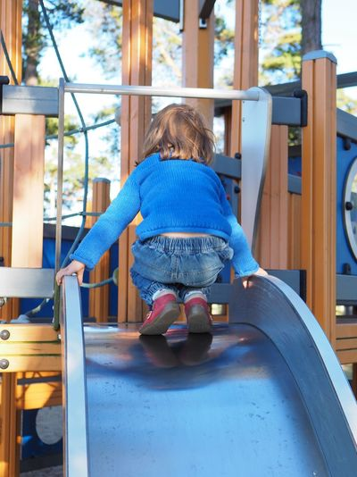 Childhood One Person Child Real People Full Length Leisure Activity Playground Lifestyles Girls Casual Clothing Outdoor Play Equipment Females Women Day Playing Slide - Play Equipment Sitting Innocence Jungle Gym Hairstyle Backwards  Up Climbing Blue