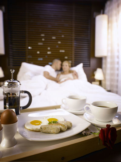 Couple Lying On Bed With Breakfast In Foreground