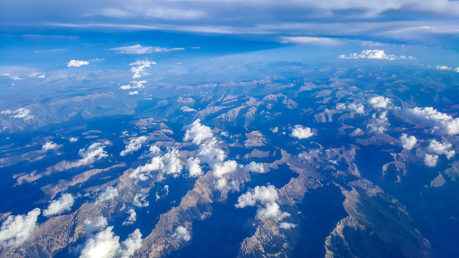Aerial view of sea and mountains against blue sky