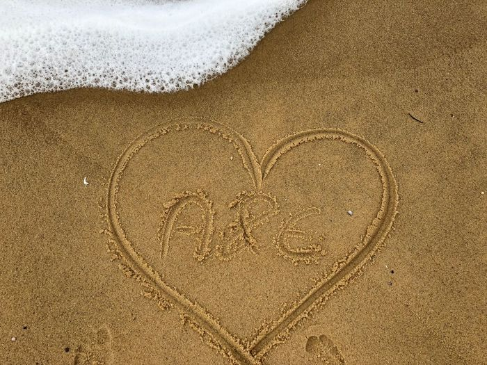 High angle view of alphabets in heart shape on sand at beach