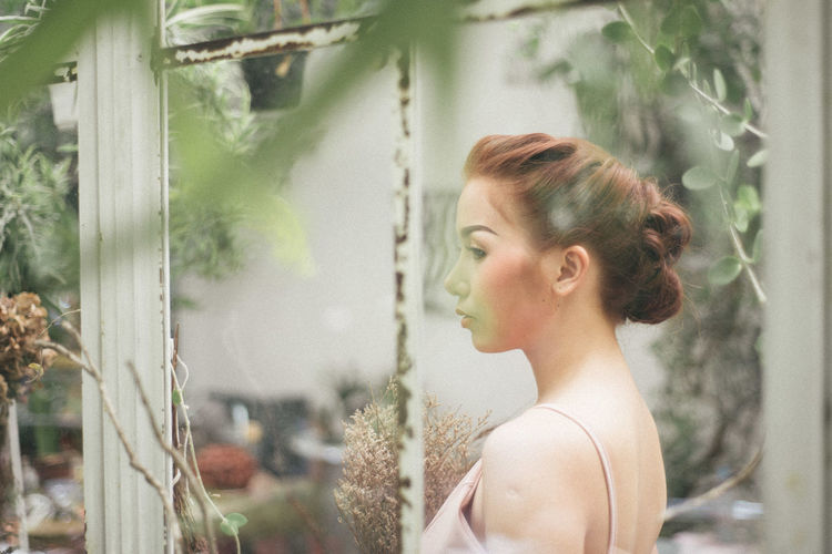 Young Woman Looking Looking Through Window