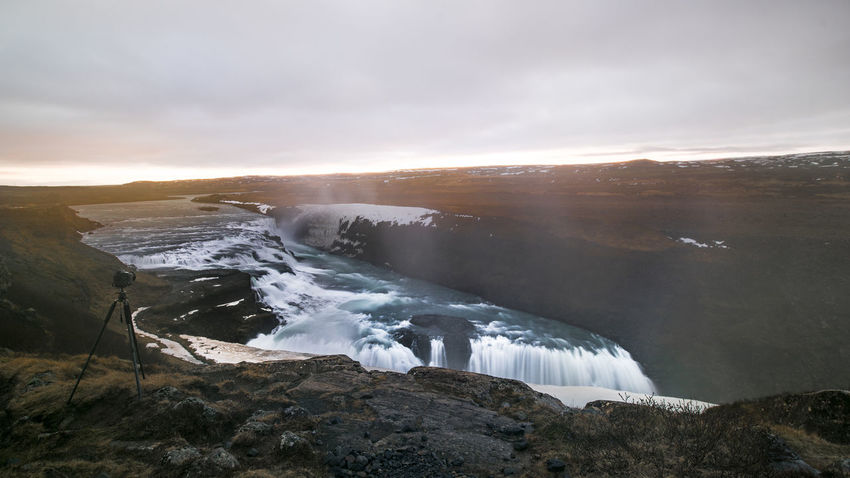 It was my first night in Iceland. I camped near Geisir at Geisir camp ground. The owner was very cool. He said it was free for me, as this is an offseason. In fact, I was the only one at the camp site. I had an amazing night, experiencing silence and complete darkness. There is something very soothing about being in the middle of nature, replying on lights from space only. The next morning, I did a short drive to Gullfoss, to catch the sunrise, also to avoid tourists. I was the first one at the scene, and it sure was worth it. During the whole stay of one week in Iceland, I have not witnessed strong sunrise or sunset, due to rain. This faint sunlight spreading over Gullfoss, though, was worth it. Beauty In Nature Cold Temperature Early Morning Gullfoss Ice Iceland Landscape Loud Mountains Nature No People Outdoors Powerful Relaxing Rocks Scenics Snow Sun Sunrise Sunset Travel Travel Destinations Waterfalls Winter Winter The Great Outdoors - 2017 EyeEm Awards