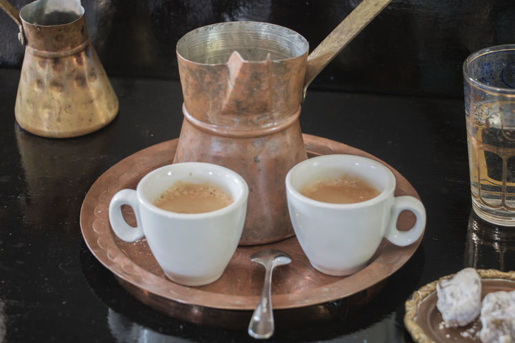 two cups of greek coffee with briki and loukumades Greek Coffee  Briki Coffee Coffee - Drink Cup Cups Drink Drinking Glass Eating Utensil Food Food And Drink Glass Household Equipment Indoors  Kitchen Utensil Lukumades Mocca Mug No People Spoon Still Life Sweet Food Table Watherglass Wood - Material