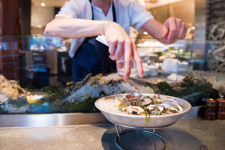 Midsection of man hand over oysters on table at restaurant