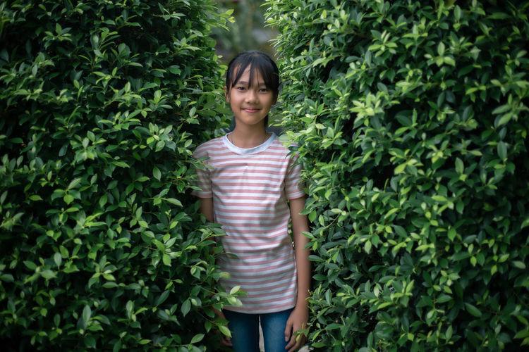 Portrait of woman standing against plants