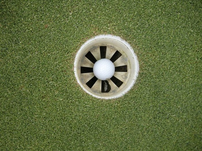 Directly Above View Of White Golf Ball In Hole On Course