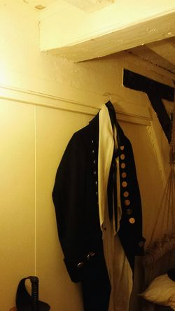 Indoors  Old-fashioned Uniform Hanging Illuminated Glow Below Deck Built_Structure Wooden Beam Interior Officers Quarters Frigate Naval Ship Historic Bedroom Museum