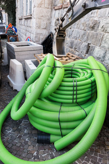 Roll of plastic pipe for road works. Protection of electric or telephone cables Green Color Day No People Outdoors Stack Container Plastic City Built Structure Footpath Street Building Exterior Nature Wall Connection Tied Up Building Construction Industry Roadwork Site
