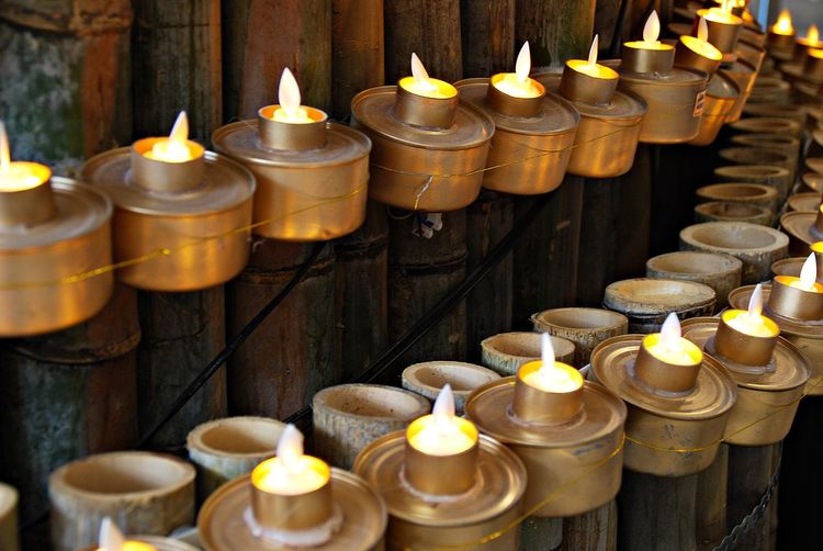 Lit Oil Lamps Mounted On Bamboo Fence