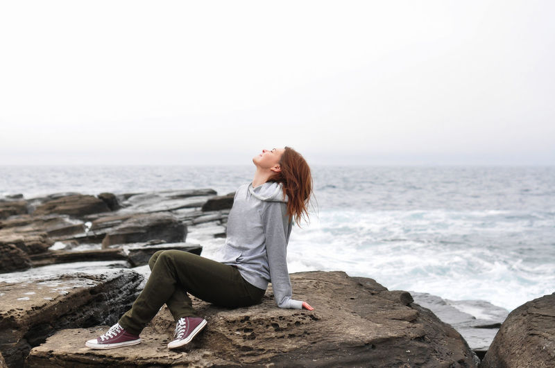 Young woman in hoodie, jeans sits on rocks near the stormy oceans with waves. local tourism