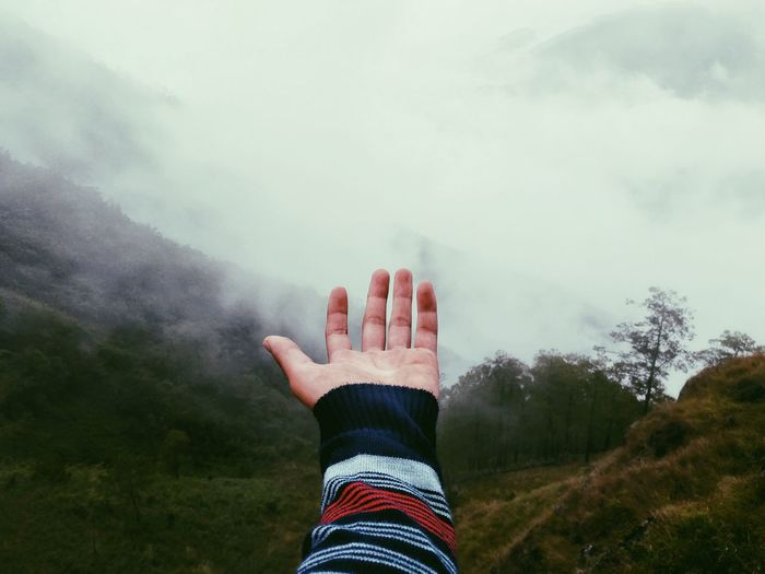 Cropped Hand Against Mountains During Foggy Weather