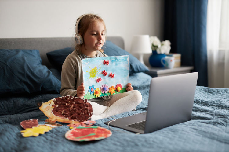Little girl preschooler learning online showing her works drawings done at home