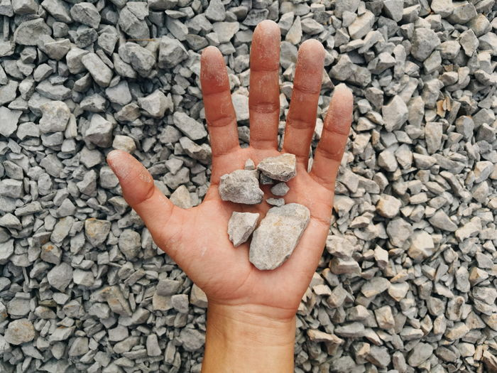 Close-up of human hand on rocks