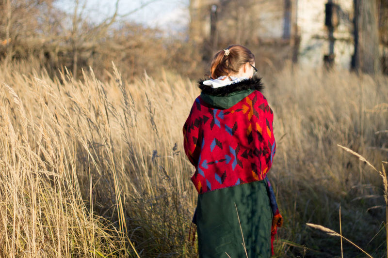 Rear view of woman standing on field during winter