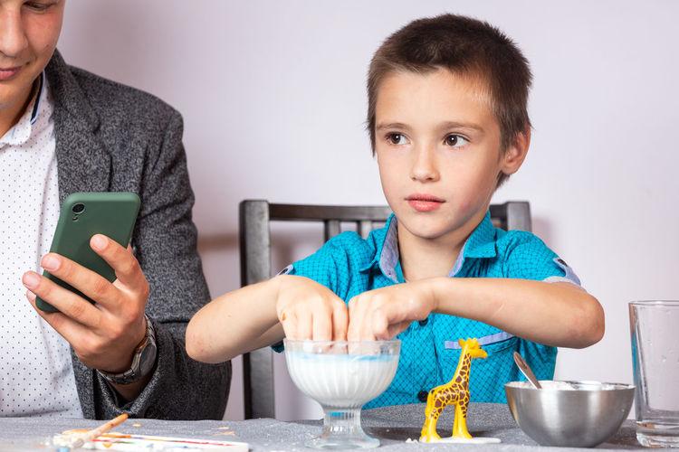 Portrait of boy holding ice cream on table