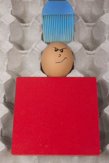Cartoon face expression at egg and red board with finger also plastic brush Angry; Anthropomorphic Face Anthropomorphic Smiley Face Blue Brush; Blue Plastic Brush; Brush; Close-up Confuse; Excited; Expression; Indoors  Joke; No People Plastic; Sad; Scare; Shy; Sick