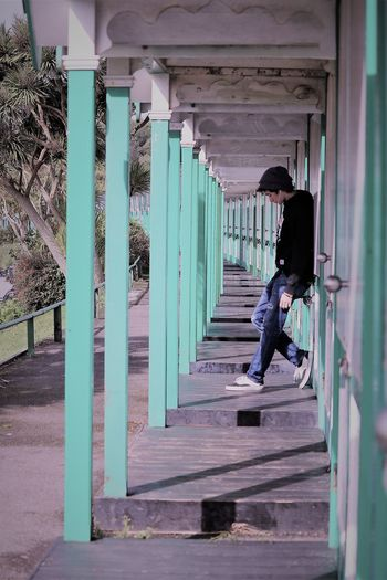 Side view of teenage boy standing by beach huts