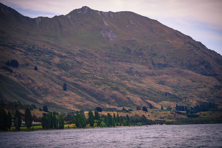 Lake Wanaka, New Zealand Architecture Beauty In Nature Day Environment Land Landscape Mountain Mountain Range Nature No People Outdoors Plant River Scenics - Nature Sky Tranquil Scene Tranquility Water Waterfront