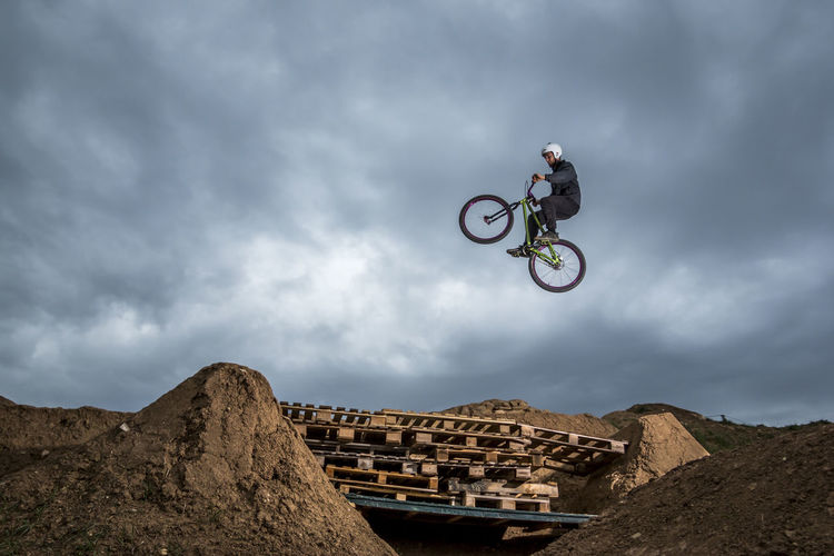Side view of sportsman jumping over hole with palettes and performing trick on bike Adventure Bike Cloud - Sky Day Dirtjump Excitement Extreme Sports Full Length Helmet Jumping Leisure Activity Low Angle View Mid-air Mode Of Transportation Motion Nature One Person Outdoors RISK Skill  Sky Sport Stunt Transportation
