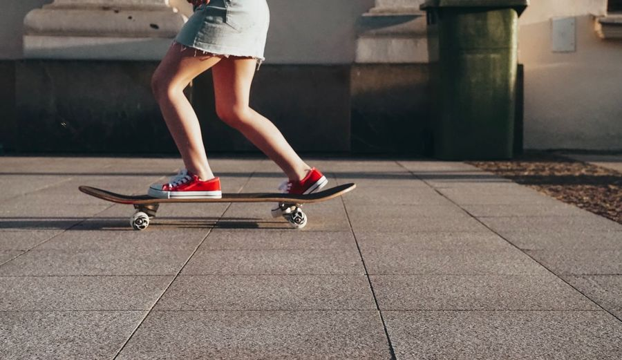 Low section of woman riding skateboard