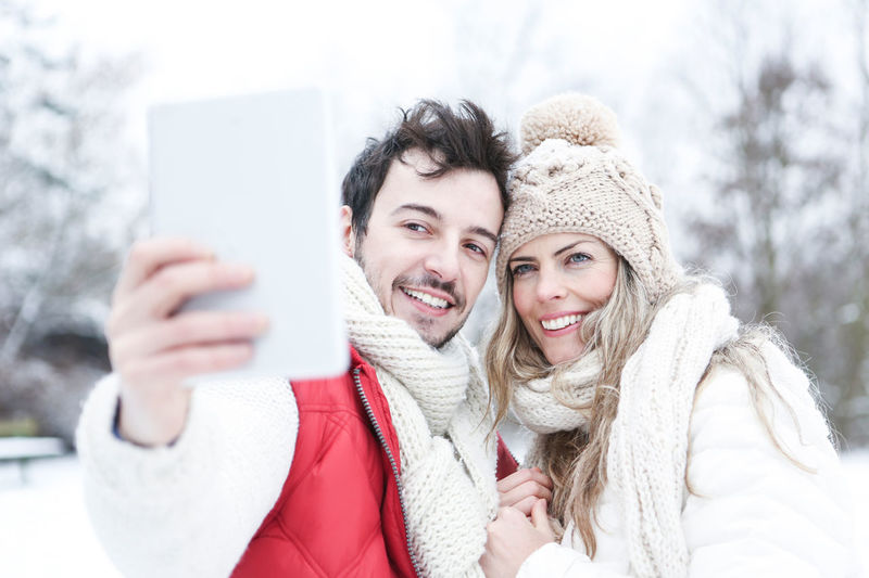 portrait of a smiling young woman in snow Adult Camera Cap Cheerfulness Chill Cold Temperature Computer Content Couple Emotion Face Feel Good Fun Happiness Happy HEAD Holiday Joy Laughing Love Man Outdoors Outside PC People Photo Messaging Photograph Photographing Photography Photography Themes Portable Information Device Portrait Positive Emotion Scarf Season  Self Portrait Selfie Ski Holiday Ski Trip Smart Phone Smartphone Smile Smiling Snow Tablet Technology Together Tourists Vacation Warm Clothing Weather White Winter Winter Holiday Wireless Technology Woman Women Young Adult Young Women