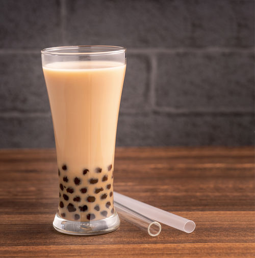 Delicious bubble milk tea with straw in drinking glass on wooden table background, concept of reduce plastic to go in Taiwan, close up, copy space Bubble Milk Tea Straw Taiwan Boba Tapioca Takeaway Ball Pearl Summer Drink Blend Mixed Food Bubbletea Take Out Away Beverage Brown Pollution Black Taiwanese Eco-friendly Environment Protection Plastic Chinese Glass Cup Disposable Wooden Background Reduce Waste Recycling Blank Plank Reusable Table Board Popular Restaurant Copy Space Closeup Design Asian  ASIA