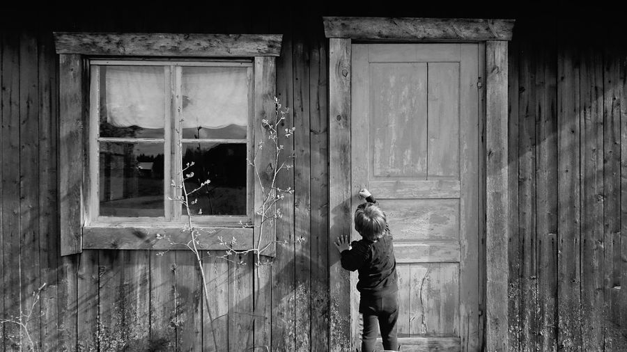 Rear View Of Boy Opening Old House Door