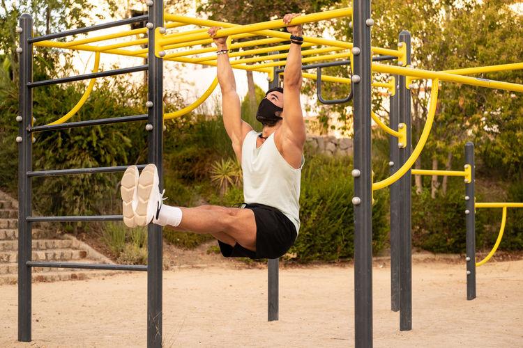Full length of senior man hanging in playground