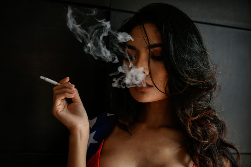 Close-Up Of Young Woman Smoking Cigarette Against Wall
