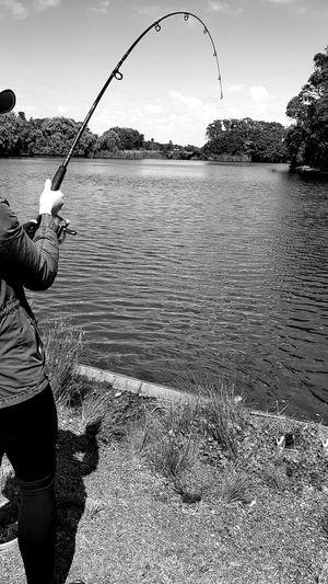 Man fishing in river against sky