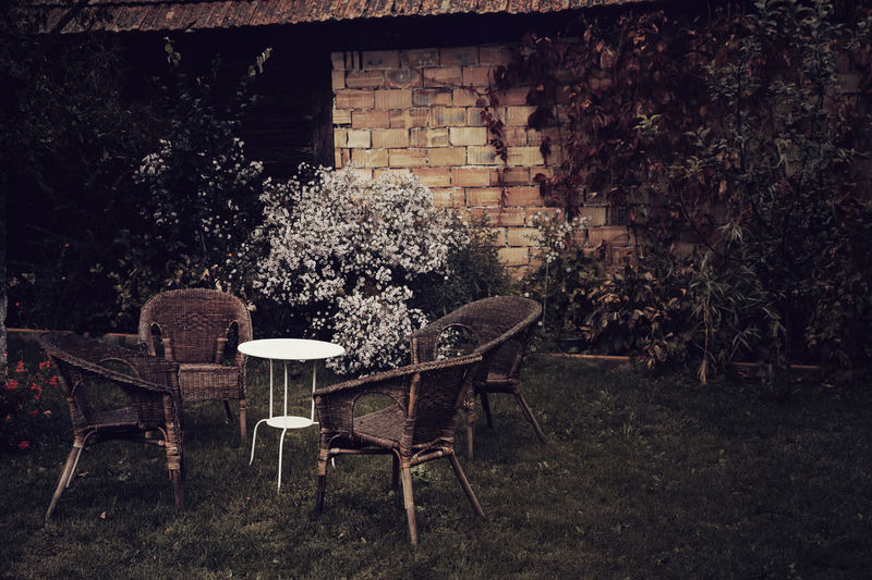 Table and chairs against wall in yard
