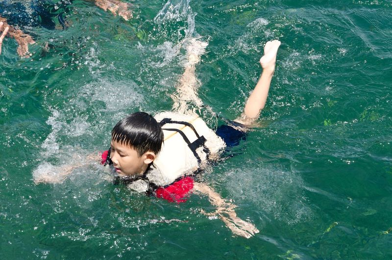 High angle view of boy swimming in sea