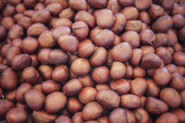 A heap of organic whole roasted chestnuts for sale in the local market. bangkok, thailand.