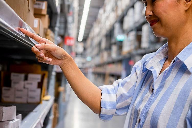 Woman pointing at shelf while standing in warehouse